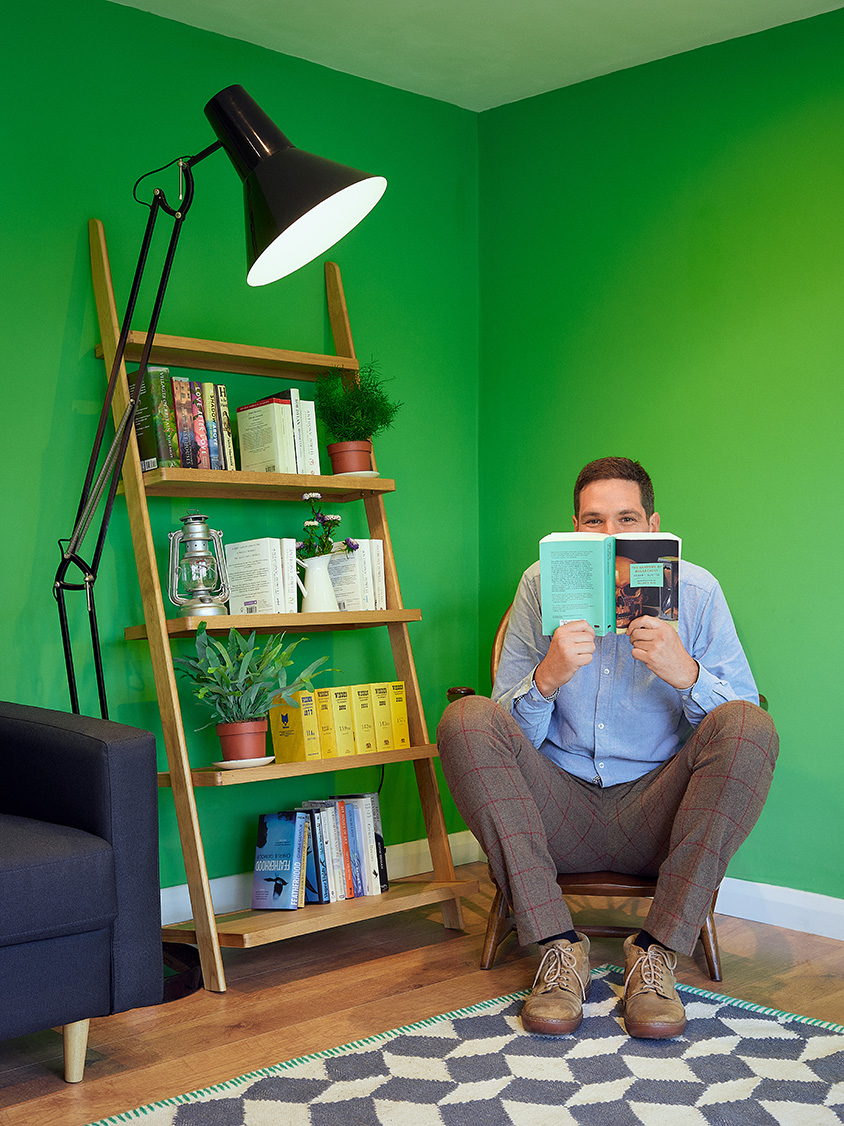 William Mandy reading a book in his home office.